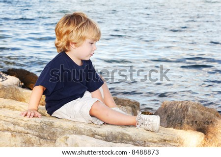 Young boy sitting by a lake