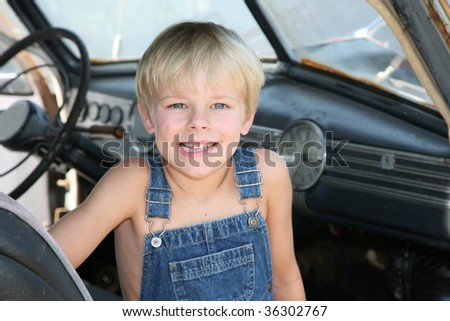 Young boy sitting in an antique car. - stock photo