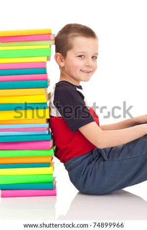 young boy sitting next to stack of books, isolated on white - stock photo