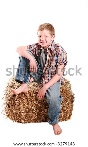 young boy sitting on a bale of hay.