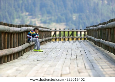 young boy sitting on a wooden path - stock photo