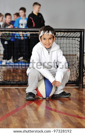 Young boy sitting on ball in front of goal - stock photo