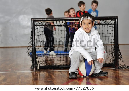 Young boy sitting on basketball,soccer goal and his friends in background - stock photo