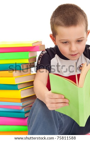 young boy sitting on floor, leaning against pile of books, and reading, isolated - stock photo