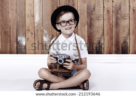 Young boy sitting on floor with camera  - stock photo