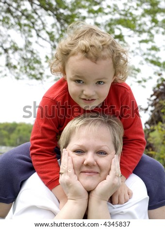 Young boy sitting on mother while on grass plot - stock photo