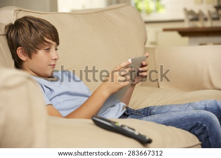 Young Boy Sitting On Sofa At Home Using Tablet Computer