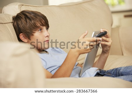 Young Boy Sitting On Sofa At Home Using Tablet Computer Whilst Watching Television - stock photo
