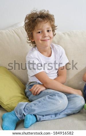 Young boy sitting on sofa looking at camera - stock photo