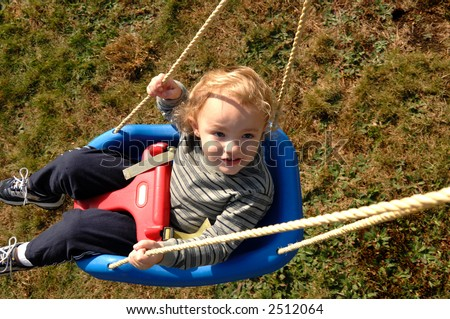 Young boy sitting on swing looking up above him - stock photo