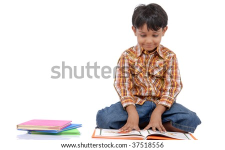 Young boy sitting on the floor reading a book against a white background - stock photo