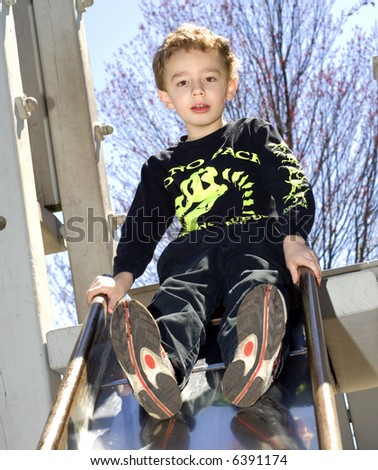 Young boy sitting on top of slide outdoors - stock photo