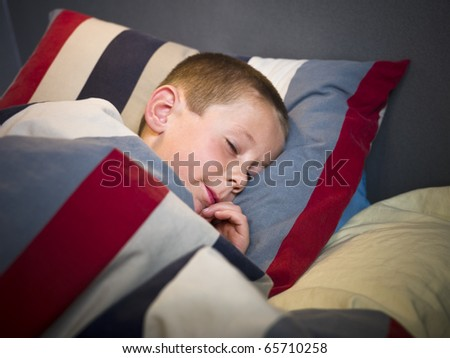 Young Boy sleeping in his bed - stock photo