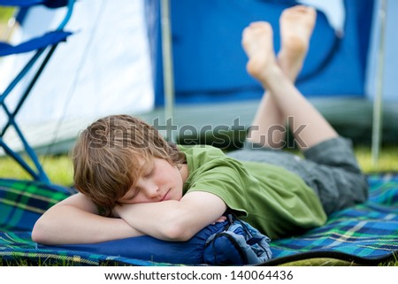 Young boy sleeping on blanket with tent in background - stock photo