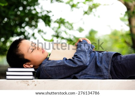 Young boy sleeping with books in the garden