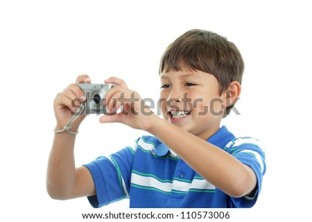 Young boy smiles as he composes a shot on his camera
