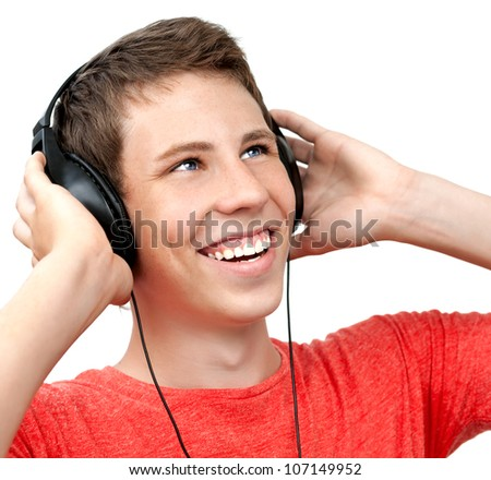 Young boy smiling and listening to music on headphones - stock photo