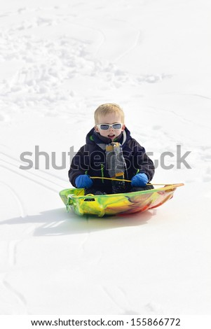 Young Boy snow sledding down a hill - stock photo