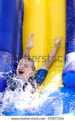 Young boy splashing water at bottom of water slide - stock photo