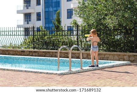 Young boy standing at the edge of a swimming pool in his bathing costume in front of an apartment block on a hot summer day - stock photo