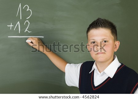 Young boy standing in front of blackboard and writing. Smiling and looking at camera. Front view