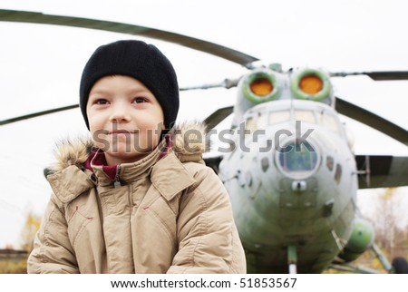 Young boy standing in front of single helicopter and dreaming about flying - stock photo