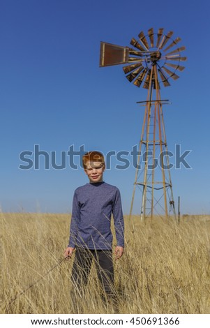 Young boy standing in the yellow grass, near an old windmill, outdoors on an agricultural farm, on a clear autumn day