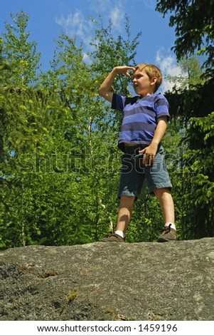 "Young boy standing on a boulder shading his eyes against the sun and looking ""towards the future""."