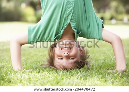 Young Boy Standing On Head In Garden