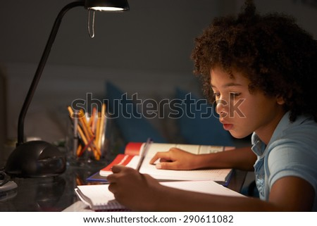 Young Boy Studying At Desk In Bedroom In Evening - stock photo