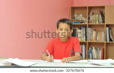young boy studying with happy face
