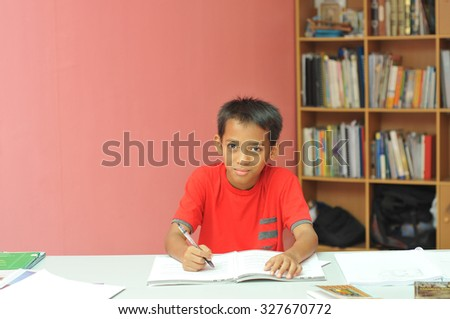 young boy studying with happy face - stock photo