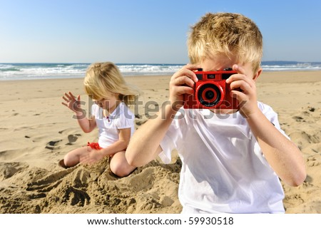 Young boy takes a picture at the beach with his red camera - stock photo