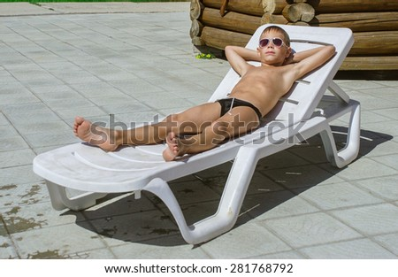 young boy taking a break from swimming and resting on a chaise lounge - stock photo