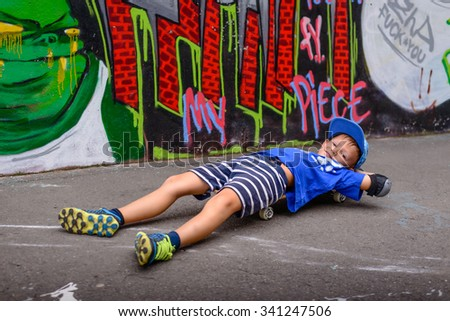 Young boy taking a nap on his skateboard lying stretched out on his back balanced on the board with his eyes closed in front of colorful graffiti wall - stock photo