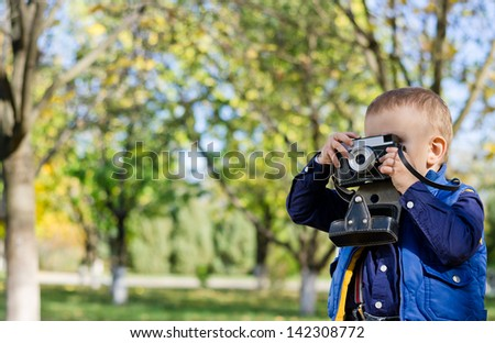 Young boy taking a photograph with a vintage film slr camera in a treed garden with copyspace - stock photo