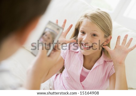 Young boy taking picture of smiling young girl with camera phone indoors - stock photo