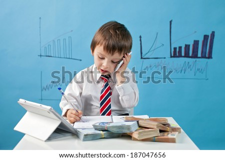 Young boy, talking on the phone, taking notes, money and tablet on the table - stock photo