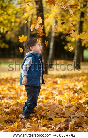 Young boy throwing leaves in autumn park
