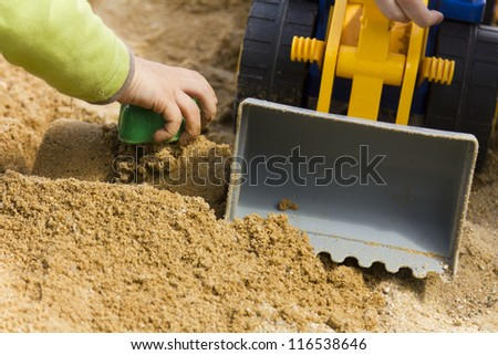 Young boy toying in a sandpit