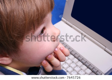 Young boy using a laptop - stock photo