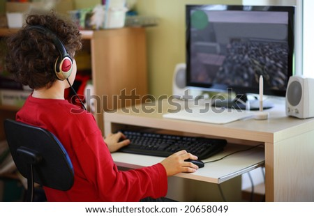 Young boy using computer at home - stock photo