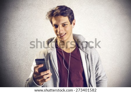 Young boy using mobile phone with earphones - stock photo