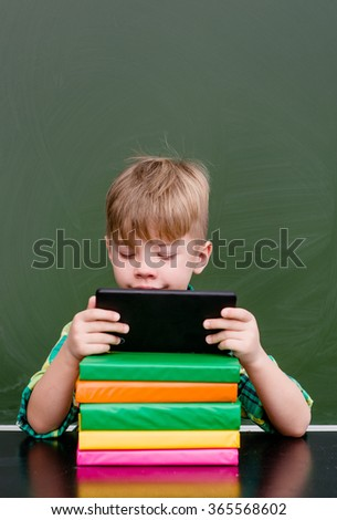 Young boy using tablet computer in school
