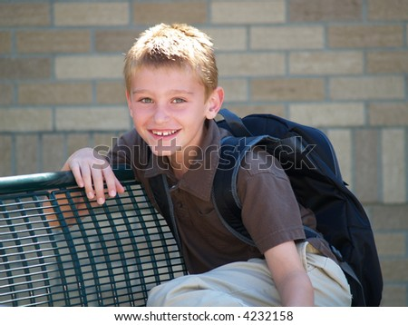 young boy waiting on a bench for the school bus - stock photo