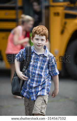Young boy walking away from a school bus - stock photo