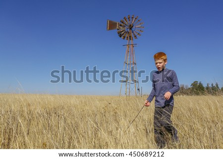 Young boy walking in the yellow grass, near an old windmill, outdoors on an agricultural farm, on a clear autumn day