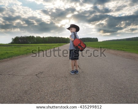 Young boy walking on a countryside road. traveler concept - stock photo