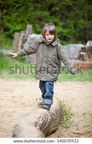 Young Boy Walking On Wood At Park - stock photo