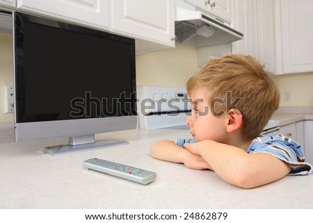 Young boy watching TV in a kitchen - stock photo